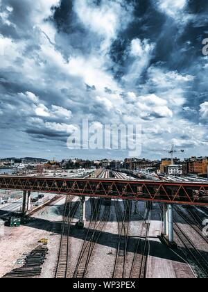 The train railways and colorful buildings under a long bridge with the background of beautiful clouds - Stock Photo