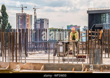 Kiev, Ukraine - September 05, 2019: Active preparatory work for concreting at the construction site of a residential building is underway. A worker wo - Stock Photo