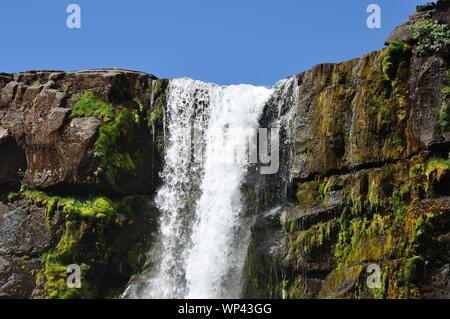 Im Nationalpark Pingvellir stürzt ein Wasserfall an der Kontinentalspalte über steile Felsen. - Stock Photo