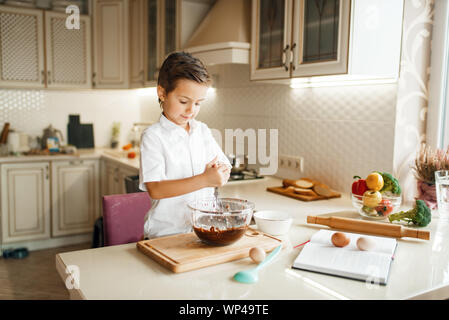 Young boy mixing melted chocolate in a bowl - Stock Photo