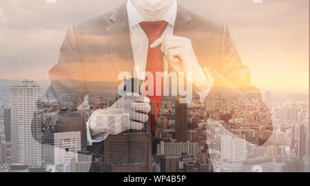 Double exposure businessman tying red necktie and cityscape in sunset - Stock Photo