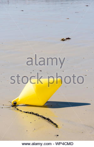 A conical yellow buoy and its anchorage chain, used as a launching channel marker, lying on the wet sand on the beach under a bright sunshine. - Stock Photo