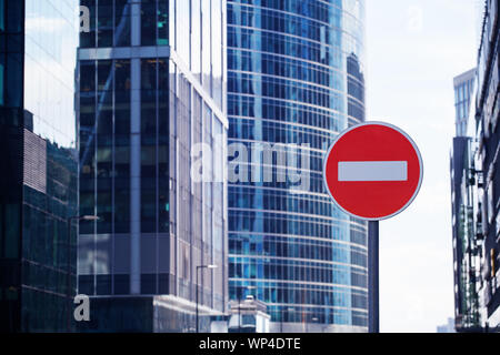 Red road stop sign or brick on city skyscrapers business center blurred background closeup, entrance prohibition, restriction, no way symbol, no entry - Stock Photo