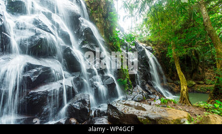 Under a cascading waterfall surrounded by lush rainforest - nature scenic landscape concept image. - Stock Photo