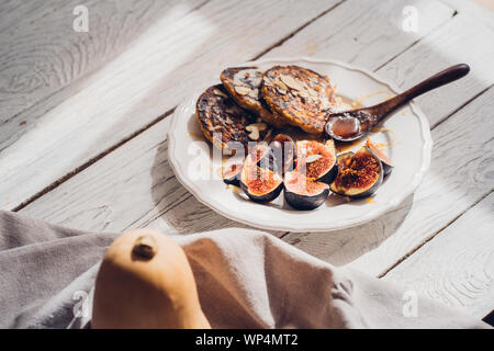 Pumpkin pancakes with figs on white wooden table. Food photography, food blogging concept, copyspace - Stock Photo