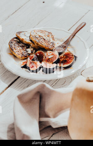 Pumpkin pancakes with figs on white wooden table. Food photography, food blogging concept - Stock Photo