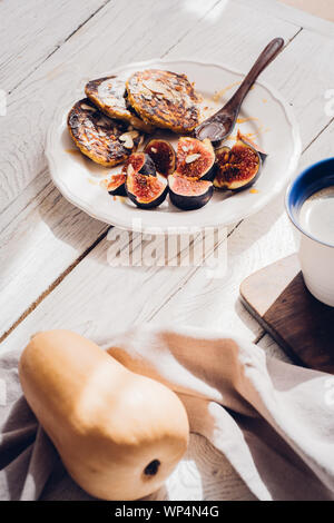 Pumpkin pancakes with figs on white wooden table. Food photography, food blogging concept, from above - Stock Photo
