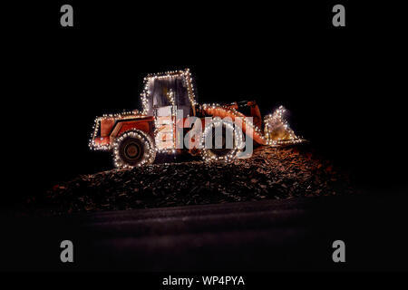 wheel loader decorated with lights at christmas - Stock Photo
