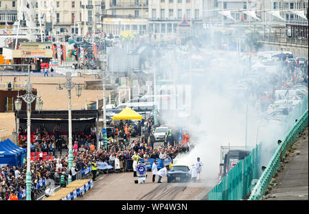 Brighton UK 7th September 2019 - Competitors send smoke billowing across the start line as they warm up their tyres in the annual Brighton National Speed Trials along Madeira Drive on the seafront . The event is run by the Brighton and Hove Motor Club and is open to cars and motorcycles old and new with some of the drivers in their eighties as well . Credit : Simon Dack / Alamy Live News - Stock Photo