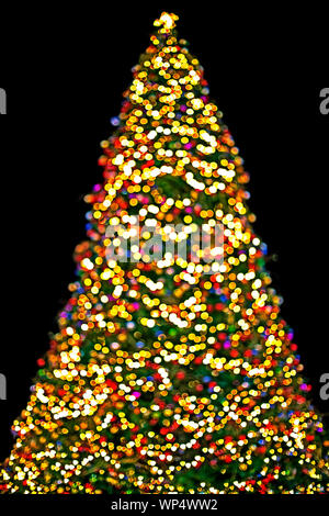 background Christmas tree with multicolored lights glowing in winter - Stock Photo
