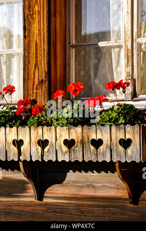 Traditional red geranium flowers in the windows of typical Alpine wooden huts. Austrian wooden chalets. Flower decoration. Tradition, style. Bavaria, Austria, Switzerland. Swiss Alps. - Stock Photo