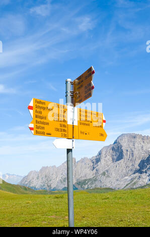 Yellow information sign in First, Switzerland giving distances and directions for hiking in the Swiss Alps. Popular paths by Grindelwald leading to Bachalpsee. Summer Alpine landscape in background. - Stock Photo