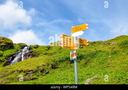Yellow tourist sign in Bachlager, Switzerland giving distances and directions to hikers in the Swiss Alps. Popular hiking paths by Grindelwald leading to Bachalpsee. Alpine stream in background. - Stock Photo
