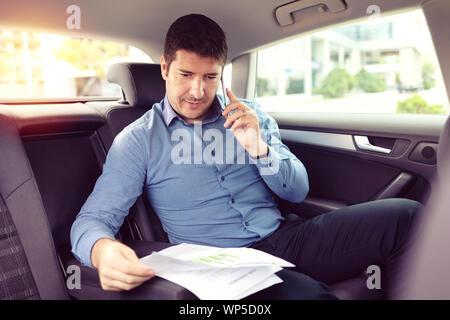 Happy smiling business man talking on phone while siting in a taxi - Stock Photo