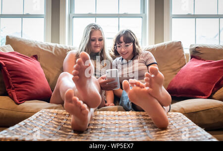 Two teenage girls sitting on couch with feet up looking at cellphone.