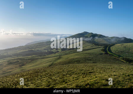early morning landscape view with sunrise and fog on the green fields at the north coast of the Azores island of Sao Jorge, as seen from the central m - Stock Photo