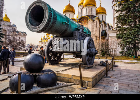 Moscow, Russia, April 2013 Tourists visiting Kremlin looking at huge old cannon, Tsar Pushka, with Dormition or Assumption Cathedral in background - Stock Photo