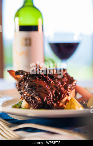 Beef spare ribs on a white plate with a bottle of red wine in the background. - Stock Photo