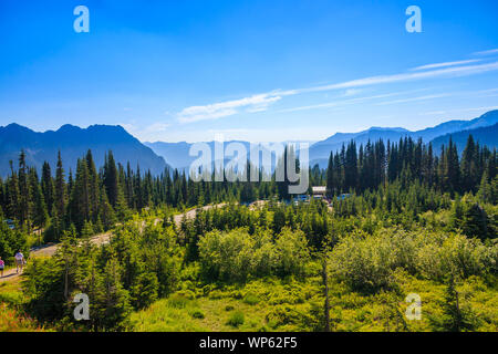 Over looking a visitor center with a hazy blue mountain range in the background, Mt. Rainier National Park, Washington, USA. - Stock Photo