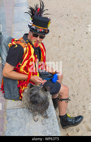 Swanage, Dorset UK. 7th September 2019. Crowds flock to the seaside town of Swanage to enjoy the dancing, with over 50 dance teams including morris dancing at Swanage Folk Festival. Morris dancer, member of Ragged Phoenix Morris sitting with dog. Credit: Carolyn Jenkins/Alamy Live News - Stock Photo