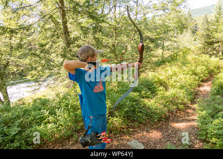 boy with cap and blue shirt shooting bow - Stock Photo