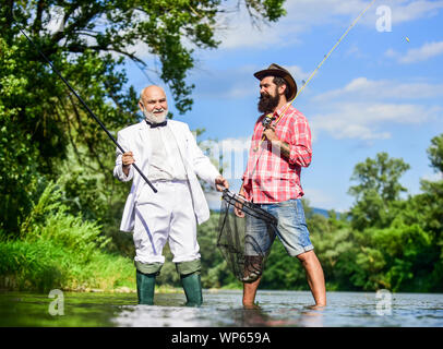 Fishing is fun. friends men with fishing rod and net. happy fishermen in water. hobby of businessman. retirement fishery. Fly fishing adventures. retired father and mature son with beard. - Stock Photo