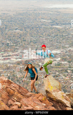 A couple of climbers in silly costumes scramble over the false summit on First Flatiron's North Arete (5.4) above Boulder, Colorado. - Stock Photo