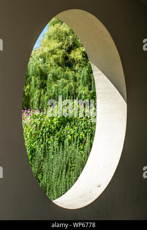 A view on a colorful garden in summer through a round hole in a concrete wall - Stock Photo