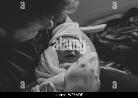 New Dad holding newborn son in hospital - Stock Photo