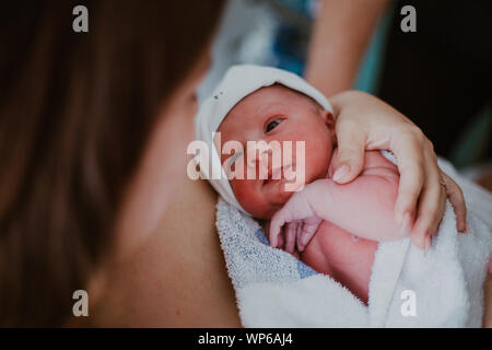Authentic birth images, woman looking at her newborn baby