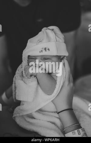 Authentic birth images, newborn baby being help by mother. Wearing a little white hat