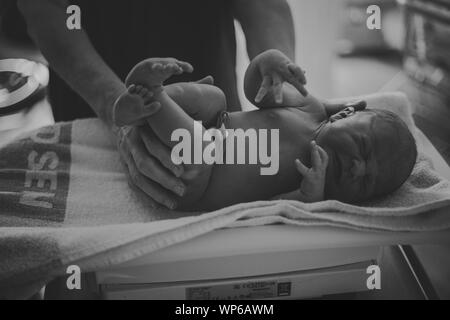 Authentic birth images, newborn baby being weighed