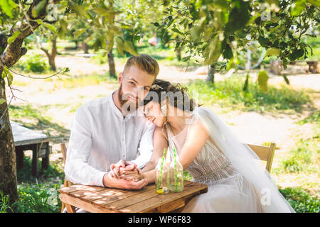 Attractive couple newlyweds, happy and joyful moment. bride and groom sit at table set for two in woods. Concept romantic date. Wedding couple sitting - Stock Photo