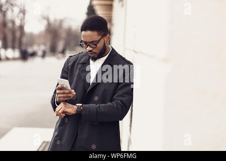 Afro businessman checking time on watches and using phone - Stock Photo