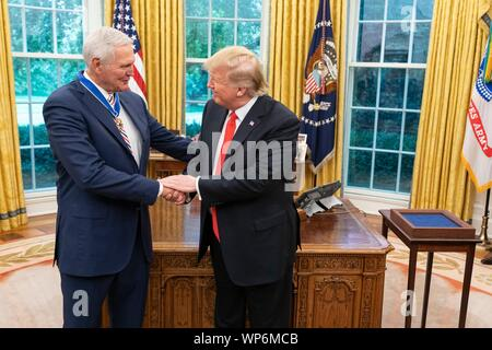 Washington, DC, USA. 05 September, 2019. U.S President Donald Trump congratulates Hall of Fame Los Angeles Lakers basketball star and legendary NBA General Manager Jerry West following the awarding of the Presidential Medal of Freedom, during a ceremony in the Oval Office of the White House September 5, 2019 in Washington, DC. - Stock Photo