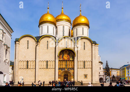 Moscow, Russia, April 2013 Tourists visiting Dormition Cathedral with majestic golden copulas or domes in Kremlin - Stock Photo