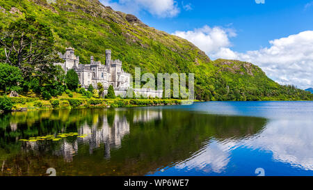 Kylemore Abbey, beautiful castle like abbey reflected in lake at the foot of a mountain. Benedictine monastery founded in 1920, in Connemara, Ireland - Stock Photo