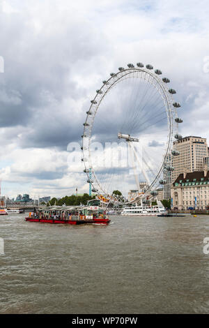 A sightseeing boat cruises in front of the London Eye - Stock Photo