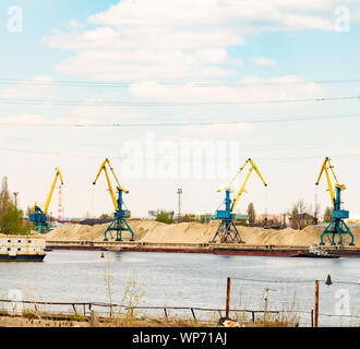 Port cranes on the river bank on a sunny day - Stock Photo