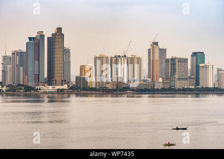 Manila, Philippines - March 5, 2019: South Harbor area early morning. Skyline with tall buildings, some under construction with with two small fishing - Stock Photo
