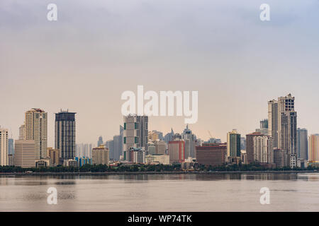 Manila, Philippines - March 5, 2019: South Harbor area early morning. Skyline with tall buildings, some under construction  form horizon band between - Stock Photo