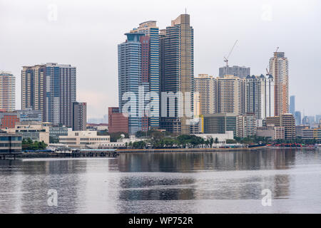 Manila, Philippines - March 5, 2019: South Harbor area early morning. Skyline with tall buildings, some under construction form horizon band between s - Stock Photo