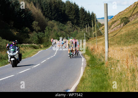 Dalmellington, Scotland, UK - September 7, 2019: Competitors in the OVO Energy Tour of Britain cycle race during stage one as they make their way through south Ayrshire towards the finish in Kirkcudbright, Dumfries and Galloway. - Stock Photo