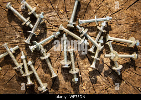 Bolts, nuts, washers on the wooden surface of an old stump - Stock Photo