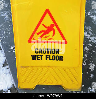 caution ice - a sign for pedestrians in the winter of yellow color with a red - black inscription - Stock Photo
