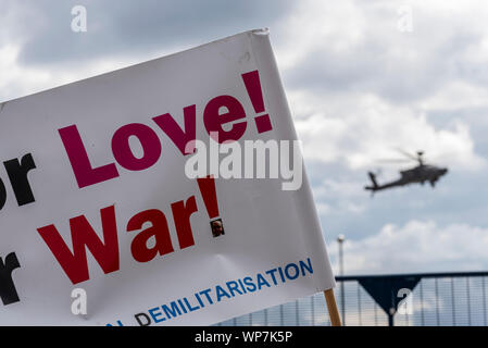 US Army AH-64 Apache gunship landing at Defence & Security Equipment International DSEI arms fair trade show, ExCel, London, UK. Protest banner - Stock Photo