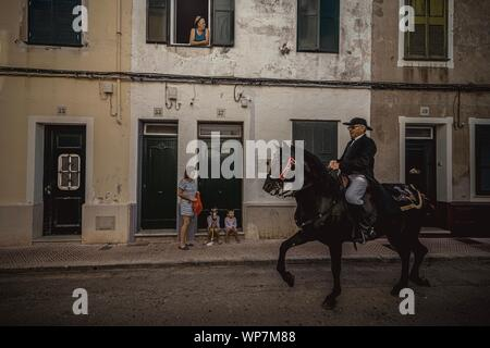 Mahon, Spain. 08th Sep, 2019. A 'caixer' (horse rider) passes two little boys with a hobbyhorse during the traditional cavalcade through Mahon prior to the 'Jaleo' at the Gracia Festival. Credit: Matthias Oesterle/Alamy Live News - Stock Photo