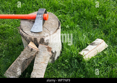 Stump with an splitting axe and firewood on the grass. Birch logs