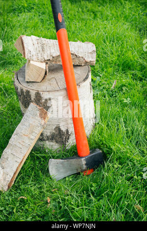 Splitting axe at a stub and firewood on the grass. Birch logs