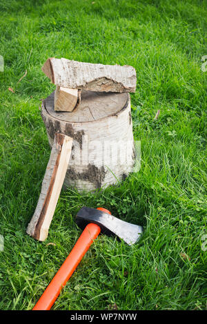 Splitting axe lying on the grass and nearby birch firewood. Preparation for winter